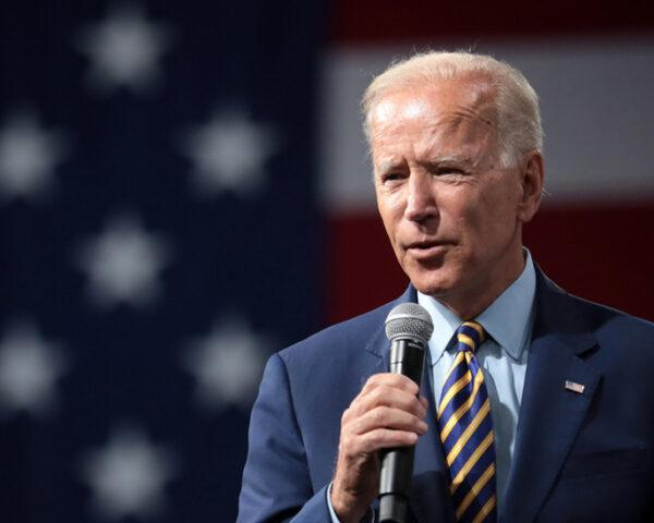 Joe Biden speaking into a microphone with American Flag in the background