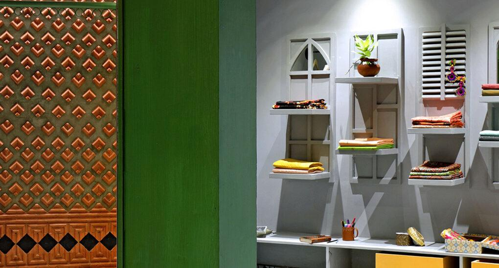 fashion boutique with green pillar, clay wall tiles and accessories hanging on a gray wall