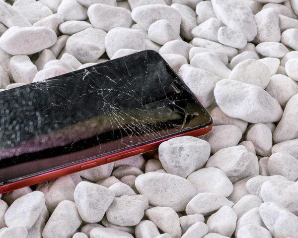 broken smartphone on white gravel