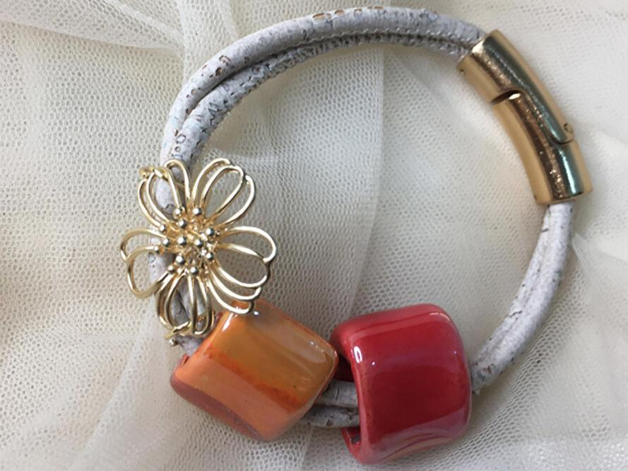 a bracelet with white cord and metallic clasp. the bracelet features a gold flower pendant and orange and red beads. there is gauzy, white fabric in the background.