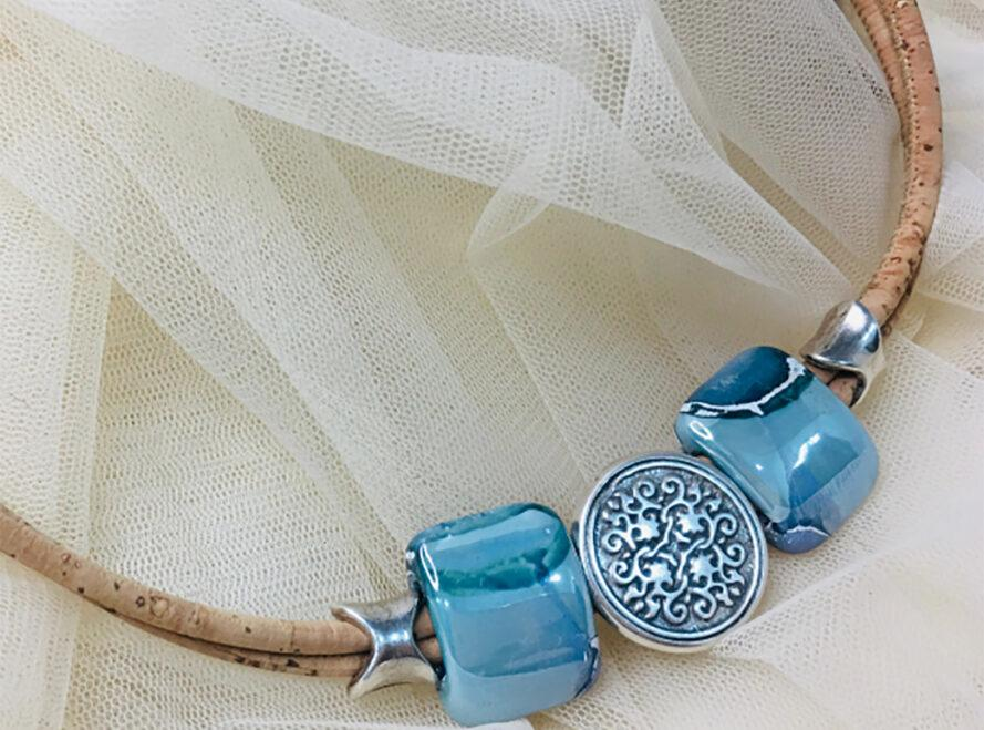 a beige cord with blue beads and a blue, circular pendant. there is gauzy, white fabric in the background.