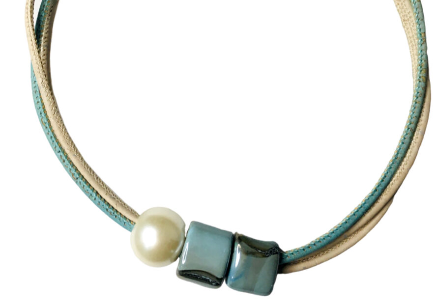 two parallel cords in blue and off-white. one pearl-like bead and two bluish, square beads.