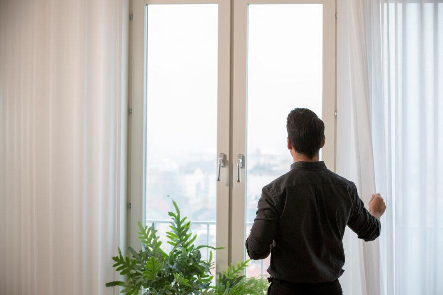 person opening sheer white curtains