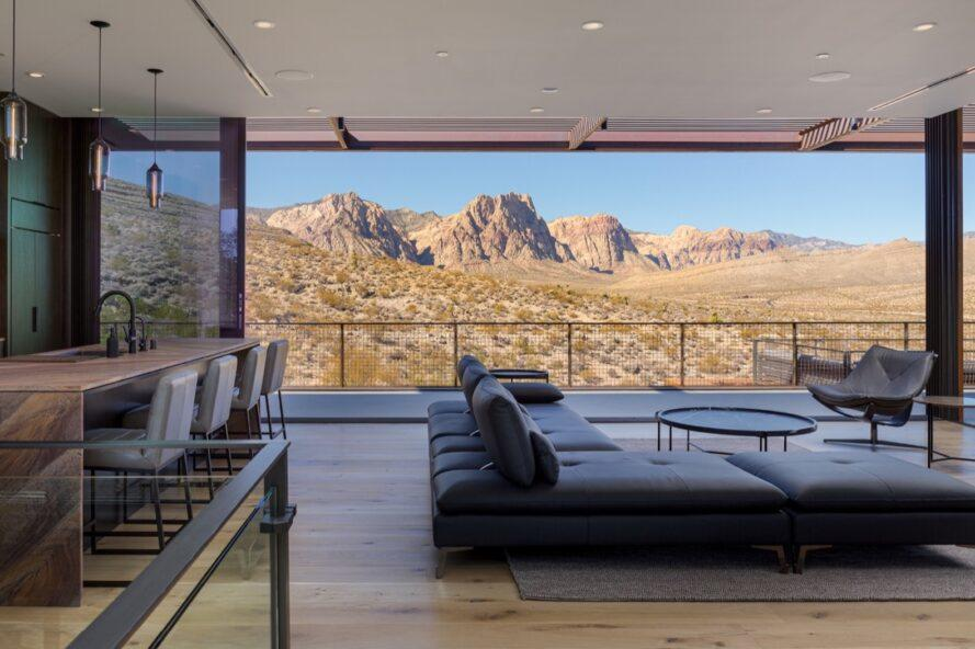 large gray sofa in room with glass wall revealing desert views