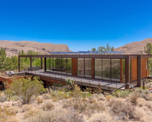 elongated weathered steel home with solar panels on roof