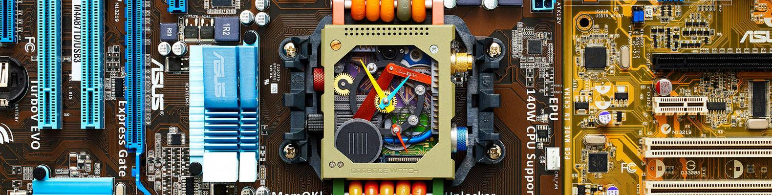 a close-up of the face of a watch with an orange band and square face. the face of the watch includes colorful mechanical parts. recycled electronic parts surround the watch.