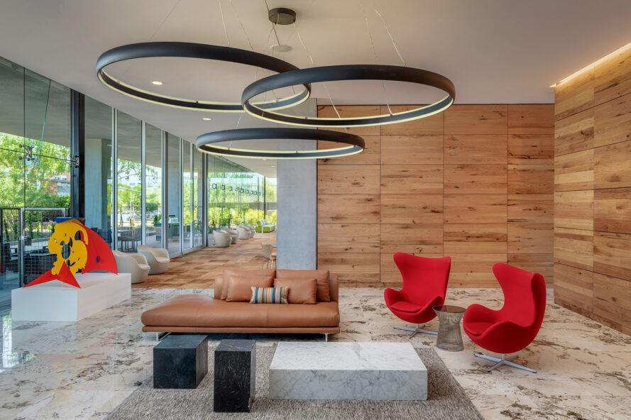 an interior sitting area with wood panel walls on the right and glass walls on the exterior wall to the left. three ringed lights hang over a piece of red and yellow modern art, a brown leather sofa and two red chairs.