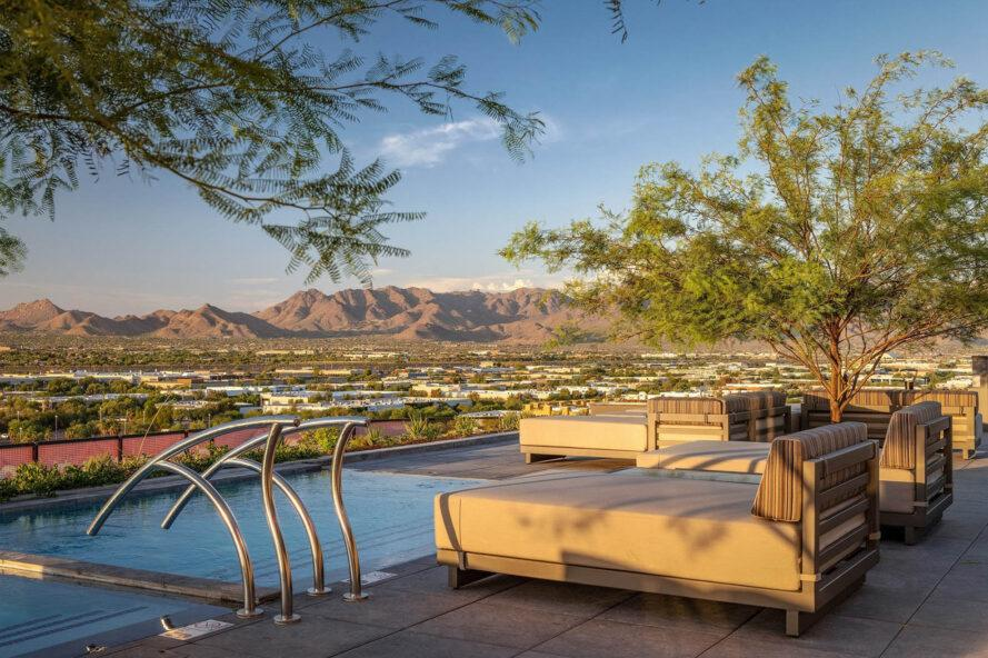 a pool with chaise lounge chairs overlooking a landscape with mountains. trees flank the the pool area.