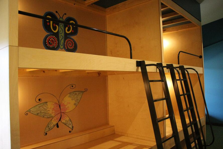 wood bunk beds with butterfly paintings on the wall
