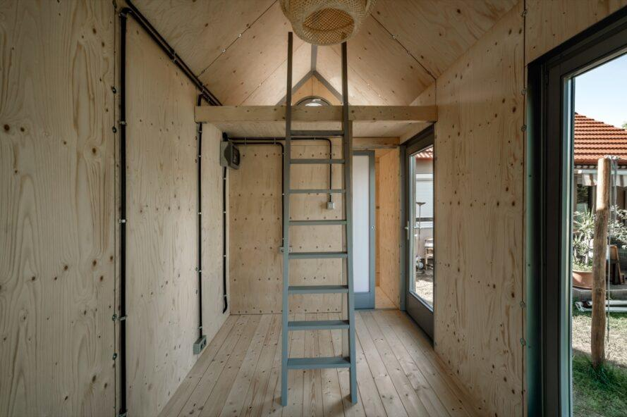 wood-lined tiny cabin interior with ladder leading to loft