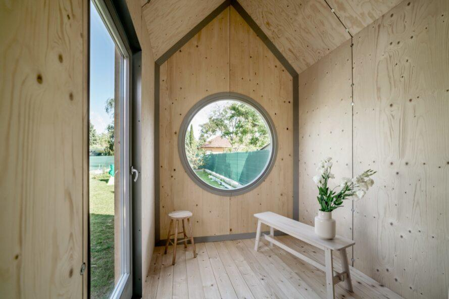 timber-lined tiny cabin interior with large round window on end wall