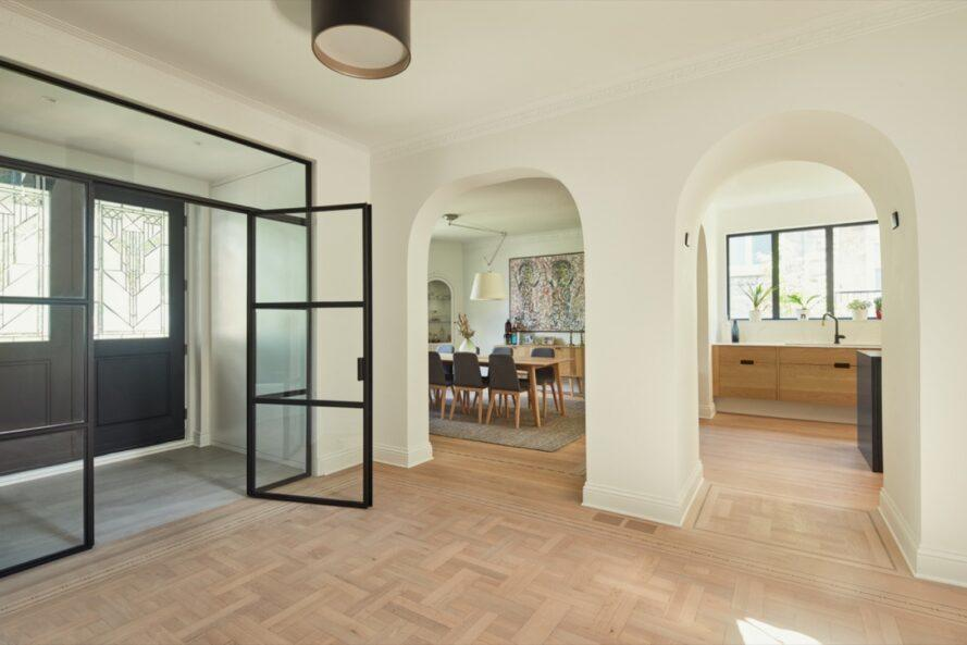 white room with light wood floors and rounded archways