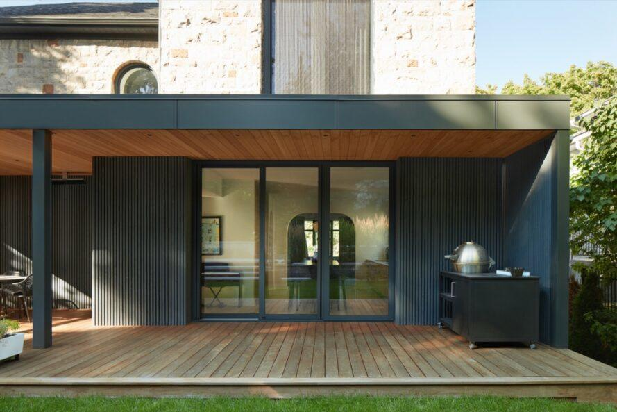 black and stone midcentury home with large wood deck