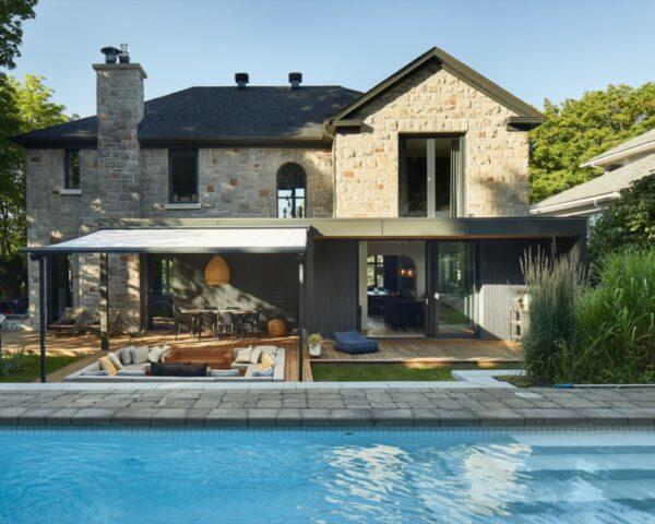 midcentury stone home with a pool