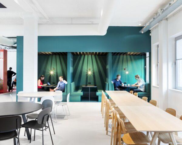 office lunch area with green booths, long wood table and smaller black round table