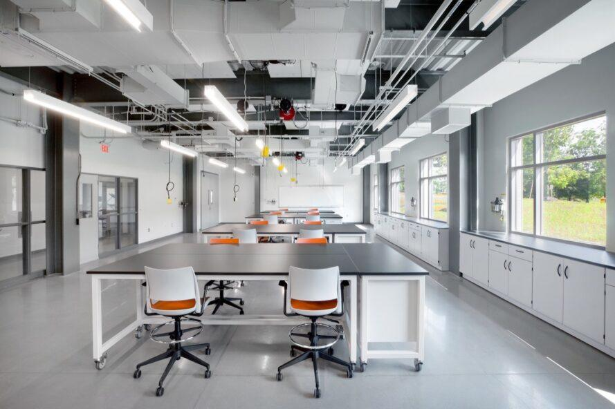 learning lab with large black tables and white and orange chairs
