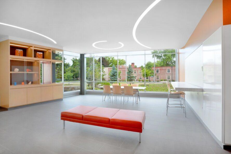 lobby with red bench, white tables and chairs and a wall of glass