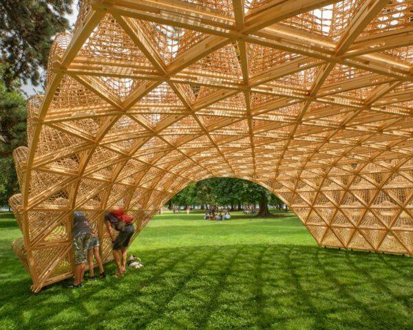 people looking through holes of a wicker pavilion