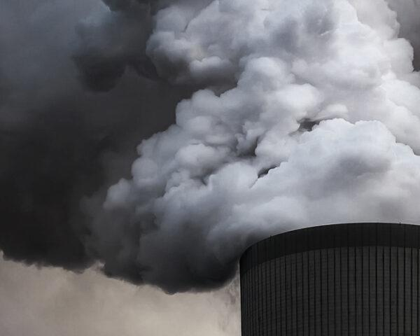 black and white image of a power plant emitting smoke into the air