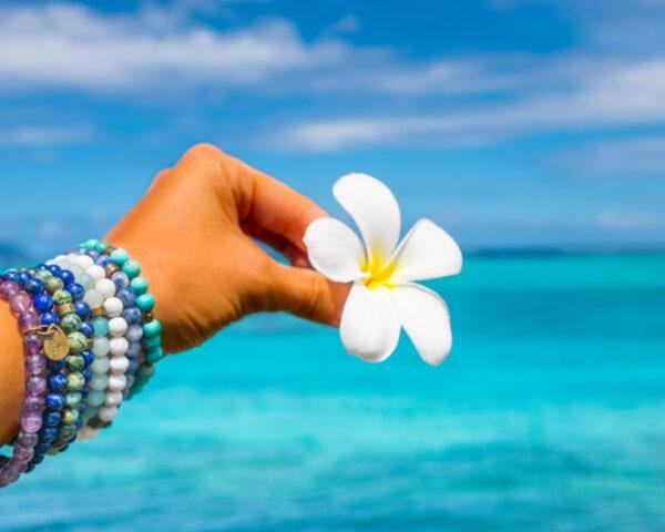 person wearing blue beaded bracelets and holding tropical flower with ocean in the background