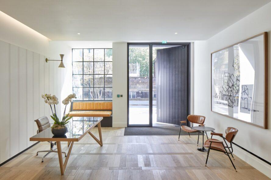 apartment with white walls, large black front door, and minimalist furniture