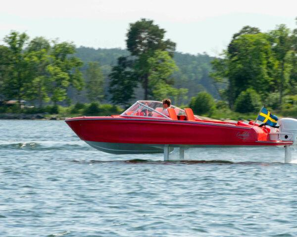 red electric boat speeding along water