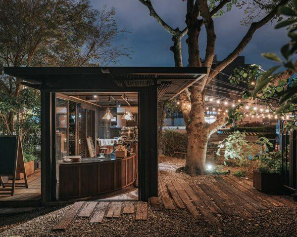 twinkle lights strung above outdoor patio next to shipping container coffee shop