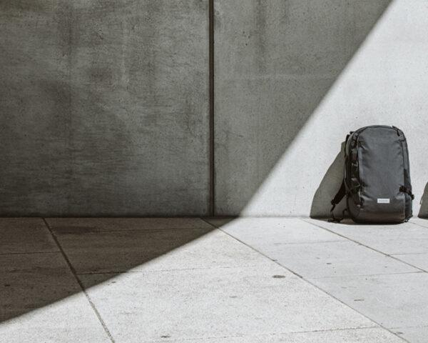 two backpacks against a concrete wall