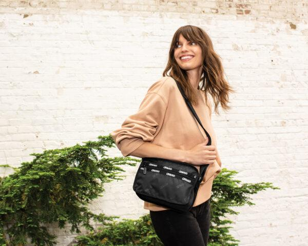a person with long brown hair and a peach-colored sweater holds a black purse that hangs on their shoulder via a long strap. in the background is a white brick wall with a green plant on the lower left.