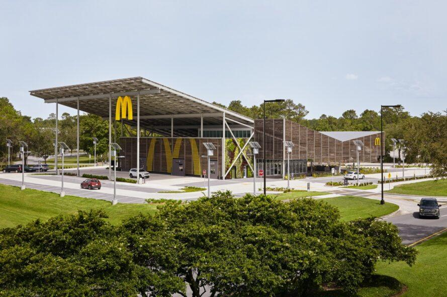 """a wide shot of a McDonald's restaurant with a sloped, v-shaped roof. a yellow """"M"""" hangs from the edge of an overhang on the building, which features a facade of wood slats."""