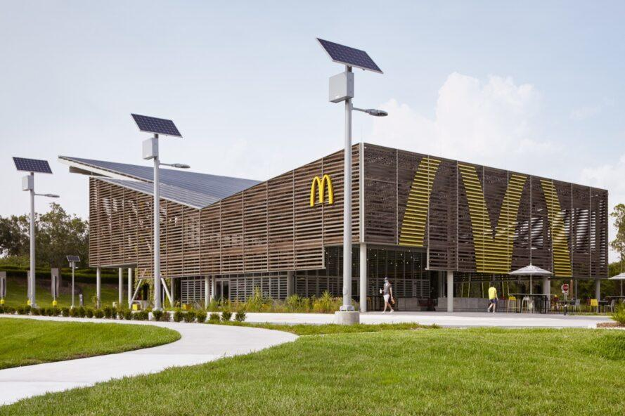 a side view of a McDonald's restaurant with a sloped, v-shaped roof. free-standing solar panels surround the building.
