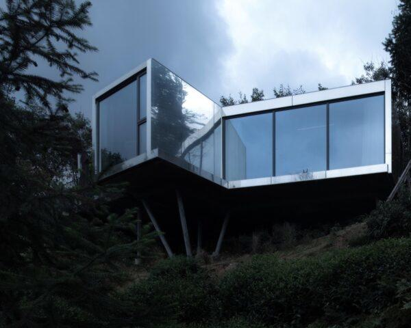 reflective metal and glass cabin on hillside