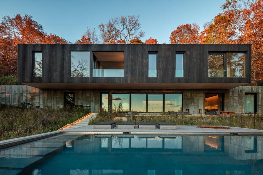 a multi-level home. the top floor has a dark timber facade with several windows of various sizes. the lower floor's facade uses concrete and features several windows. in front of the home is a pool area.