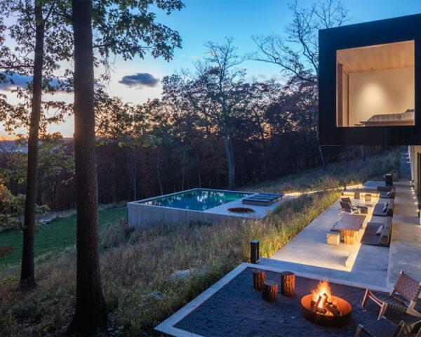 a backyard with fire pit and chairs, a pool and lounge chairs.