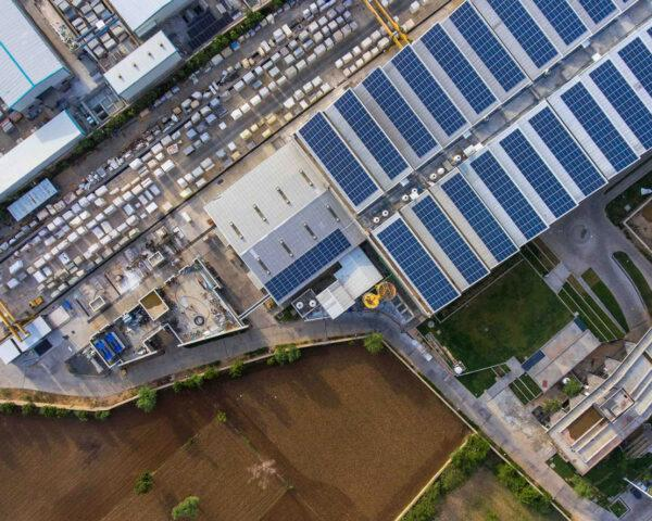 aerial view of massive industrial building covered in solar panels