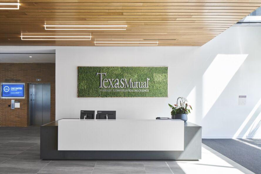 "a lobby with elevators set into a brick wall to the left. to the right are white walls with a green in-set sign reading ""Texas Mutual."" A dark gray and white desk sits in front of the green sign."