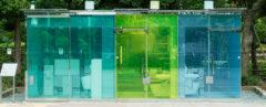 public toilet building with blue and green glass walls