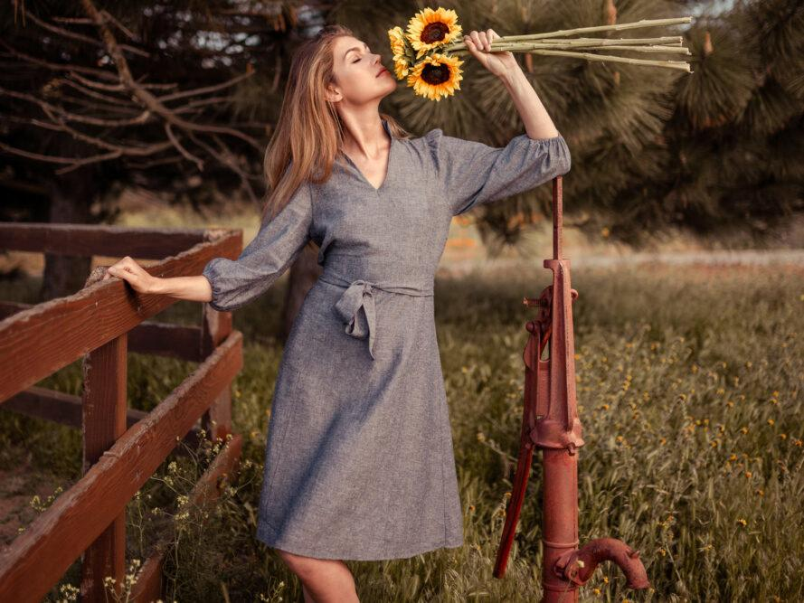 Person in gray dress smelling sunflowers