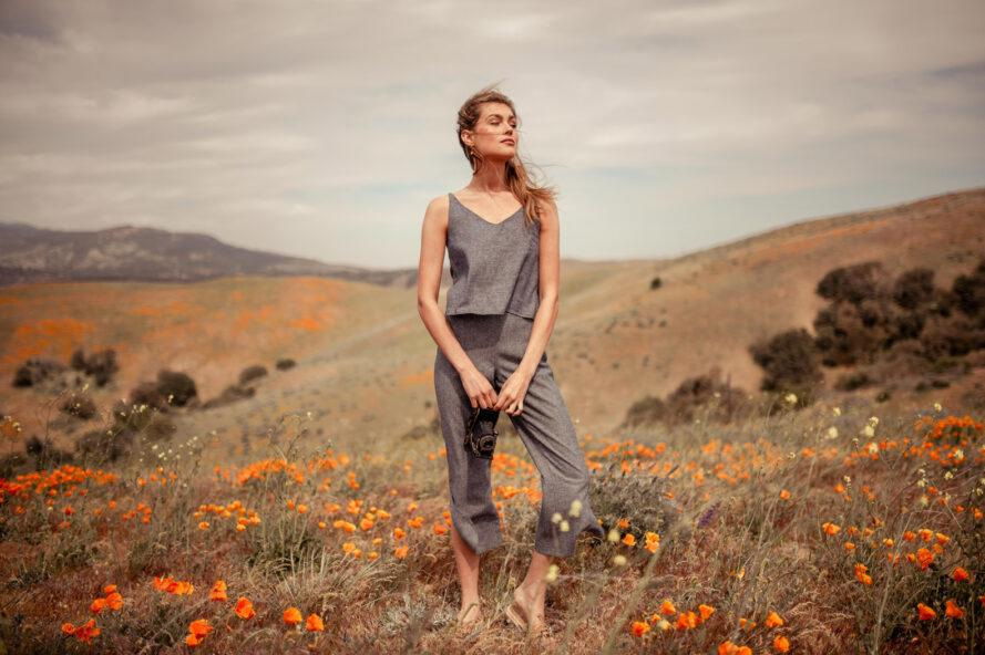 person in gray tank top and gray pants standing in a field of poppies