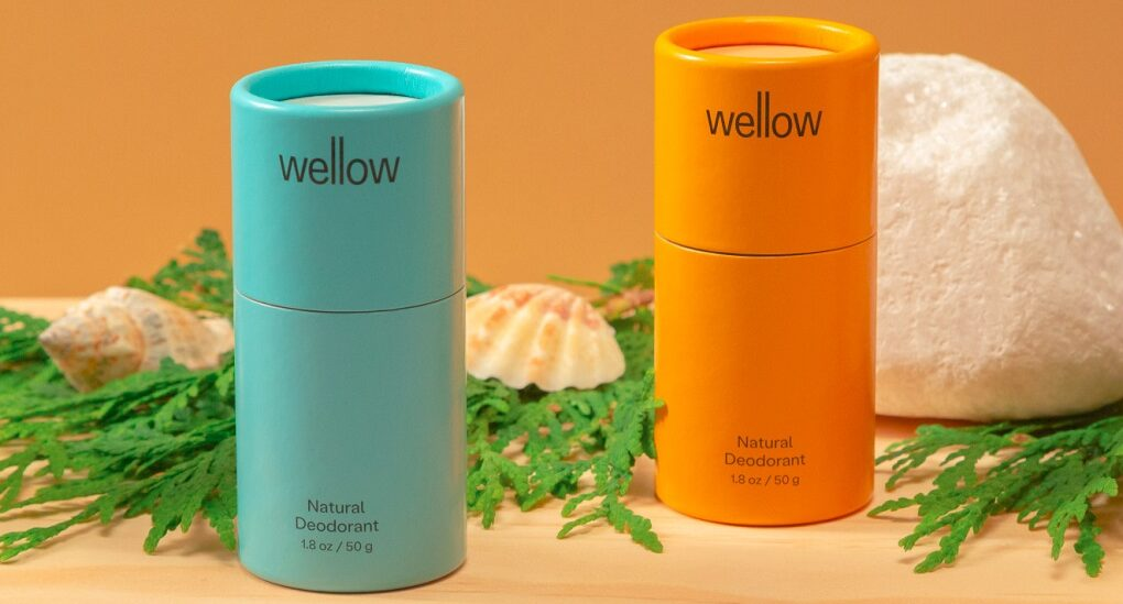 a display of four deodorant tubes. from left to right, the tube colors are gray, blue, yellow/orange and beige. in the background there are leafy green plants and a white stone.