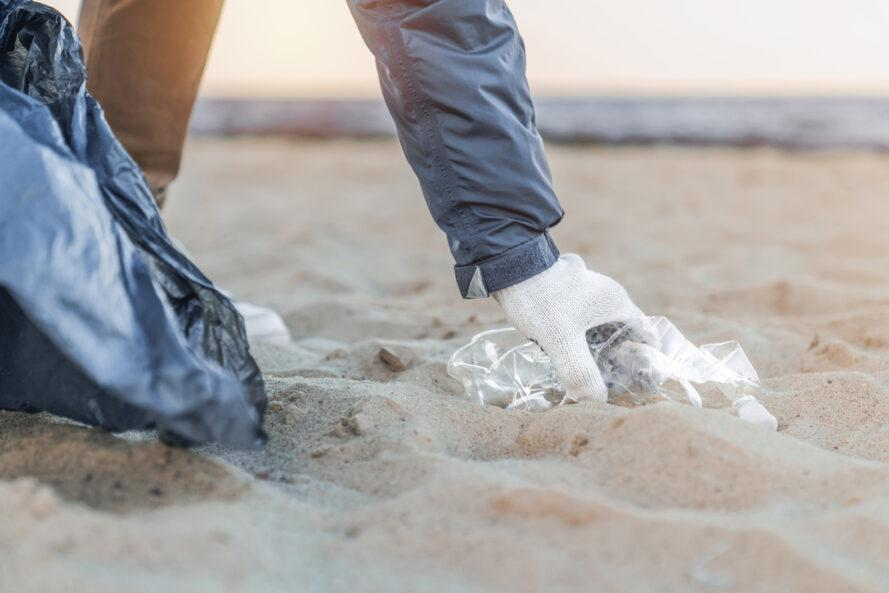 gloved hand picking up trash on a beach