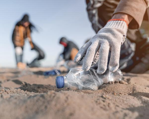 gloved hand picking up plastic bottle from sand
