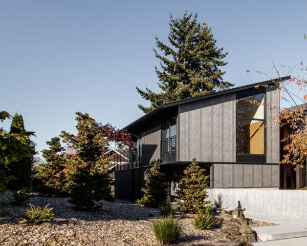 stacked gray home with slanted roof and floor-to-ceiling windows