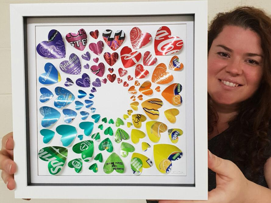 Sarah Turner holding framed art made from colorful recycled soda cans