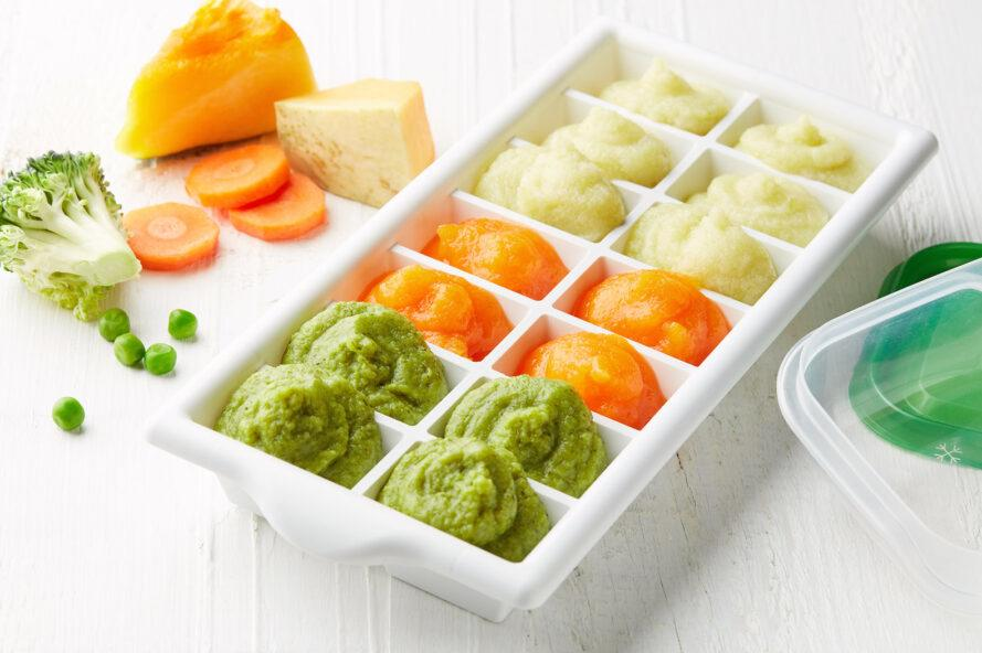 a white ice tray filled with green, orange and white baby food.