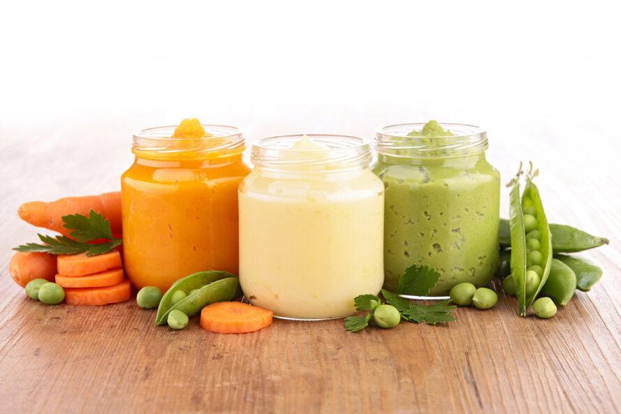 three jars of baby food. from left to right, the contents of the jars are orange, white and green. in the background, carrots and peas surround the jars.
