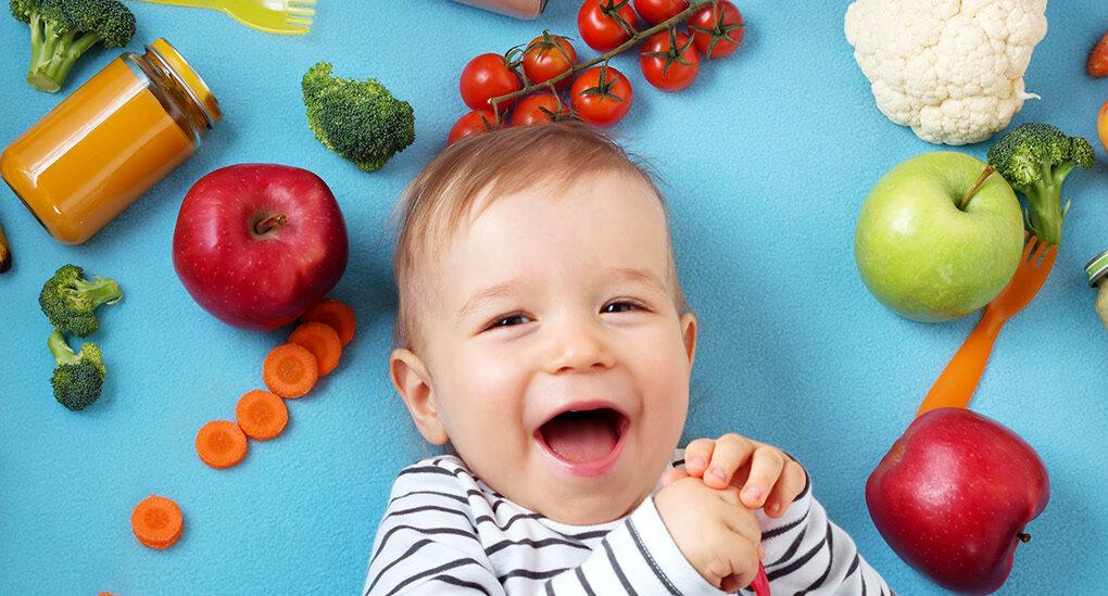a baby laying against a blue background, surrounded by various fruits and vegetables.