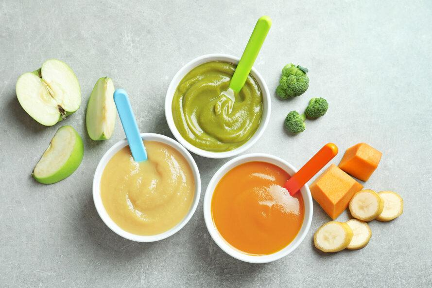 three bowls of baby food. from left to right, the contents of the jars are white, green and orange. apples, broccoli, squash and banana surround the bowls.
