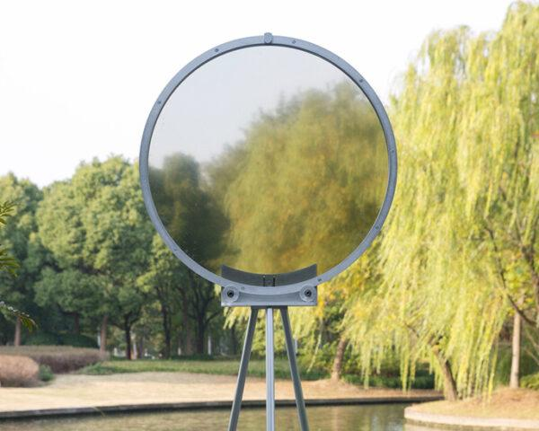 circular smog tracker device near lake with semi-transparent center