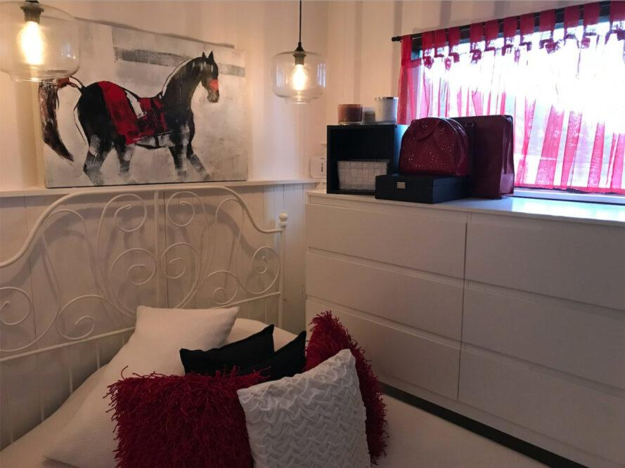 Red and white bedroom with horse art on wall